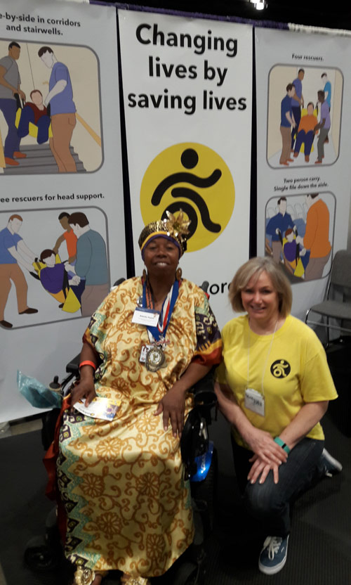 A visitor poses with Robin at the ADAPTS booth