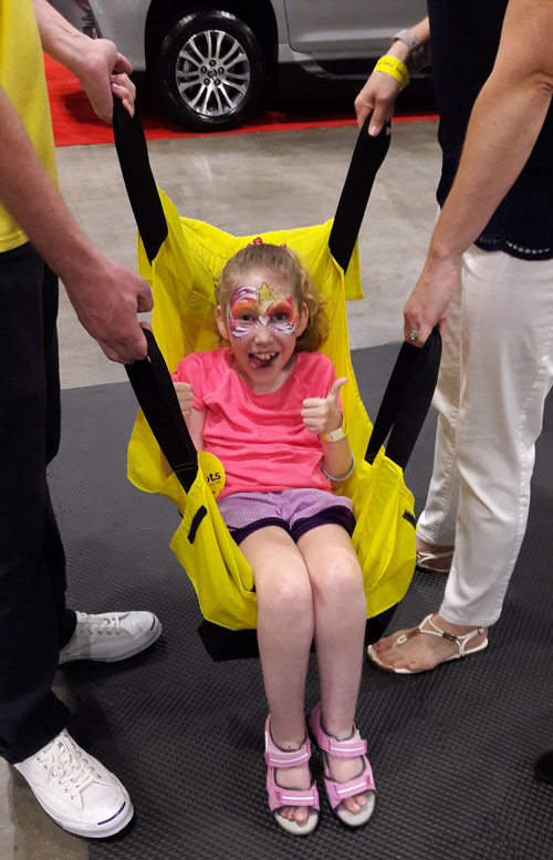 A young girl gives a thumbs up while being lifted in ADAPTS sling
